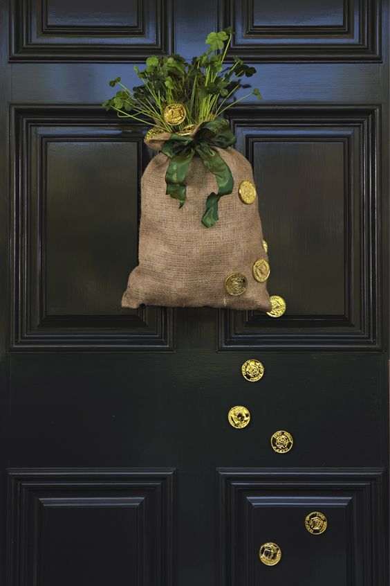 a burlap sack with fresh shamrocks, a green bow and gold coins on the sack and door