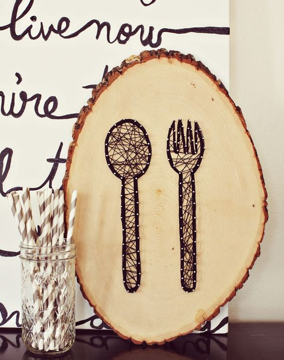 a wooden slice string artwork with a fork and a knife for a rustic space