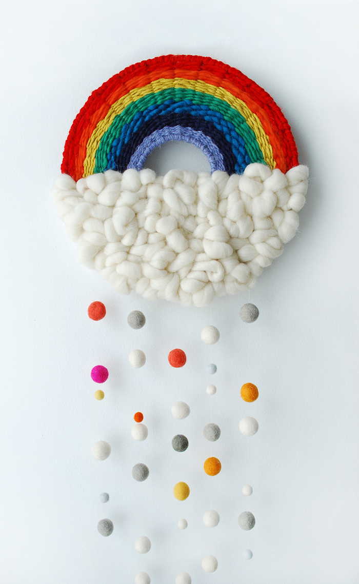 DIY bold rainbow woven hanging with pompom going down (via www.we-are-scout.com)