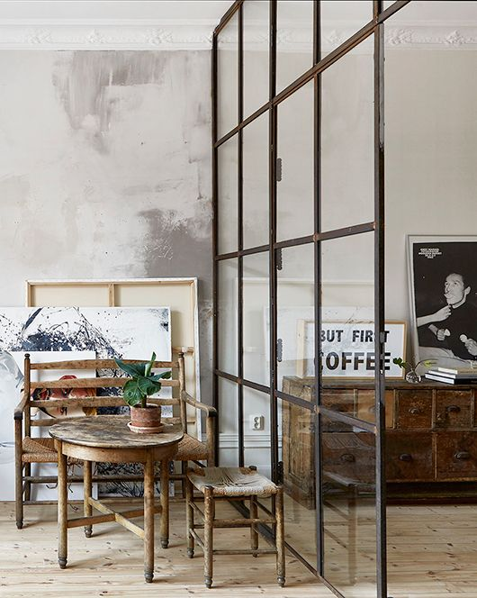 a black framed glass divider separates a small breakfast nook and the living room