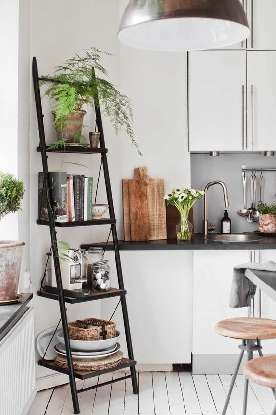 a black metal and wood industrial ladder shelf for storage in the kitchen or dining space
