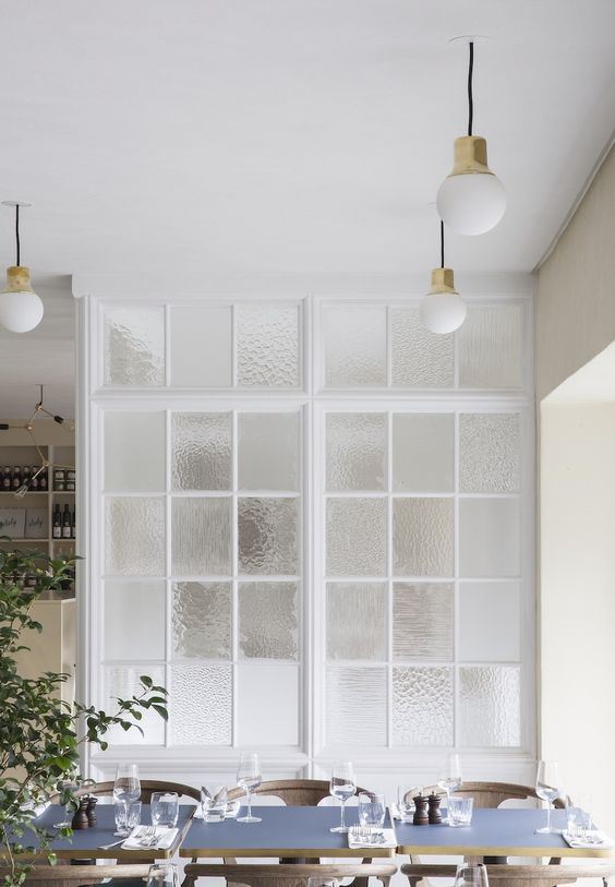 a framed frosted glass wall gently separates the kitchen and the dining room