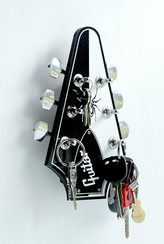 a guitar-shaped key rack is a chic way to highlight your hobbies and interests