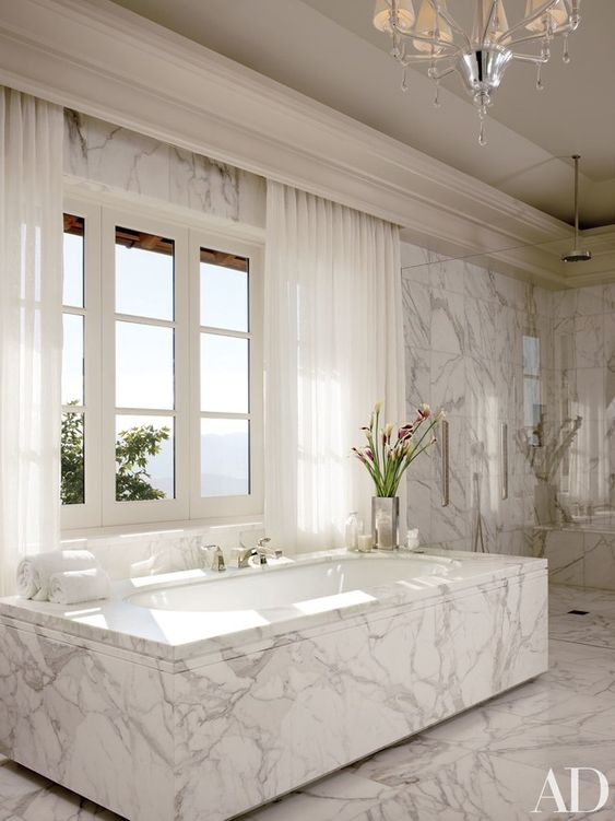 a luxurious white marble bathroom and a bathtub clad with it for a unified look