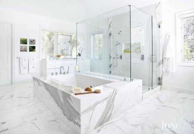 white marble used throught the space and to cover the bathtub looks very refined