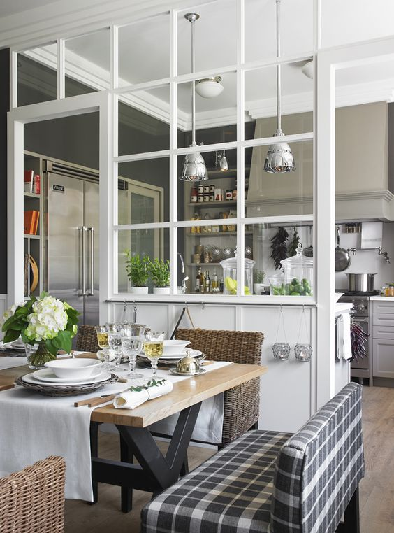 a framed glass space divider separates the dining space and kitchen very delicately