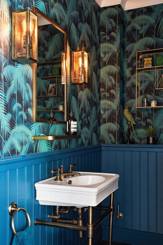 blue wainscoting and green tropical leaf print wallpaper with brass touches for a glam tropical feel