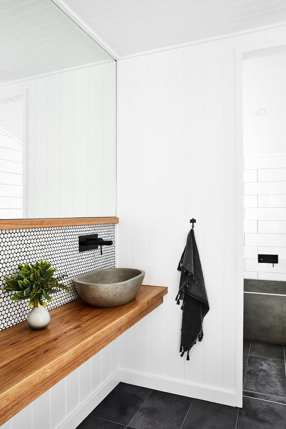 a floating wooden vanity and a white penny tile backsplash with black grout