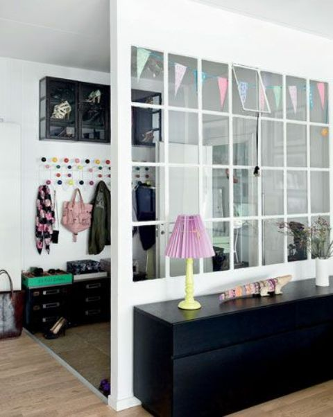 a framed glass space divider to cover the entryway lets light in and looks lightweight