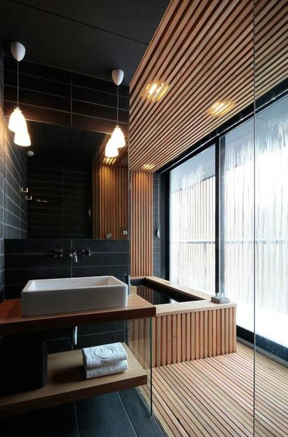 a modern bathroom clad with wood and black tiles for an edgy look