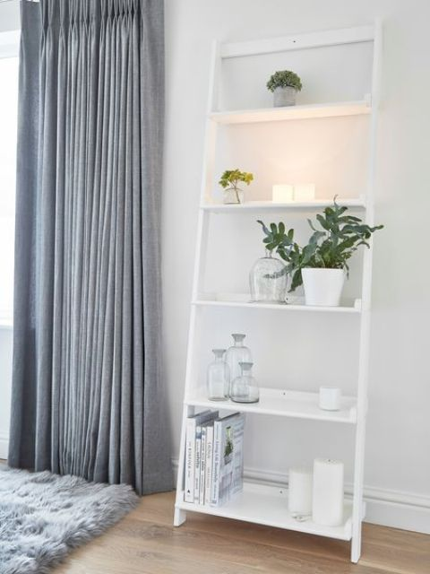 a white serene ladder with candle holders, vases, potted greenery and books for cool storage