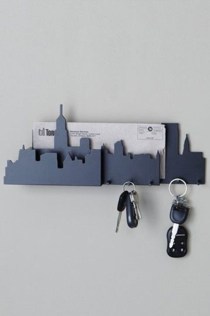 a city-shaped key rack with a mail holder and some small hooks for holding keys
