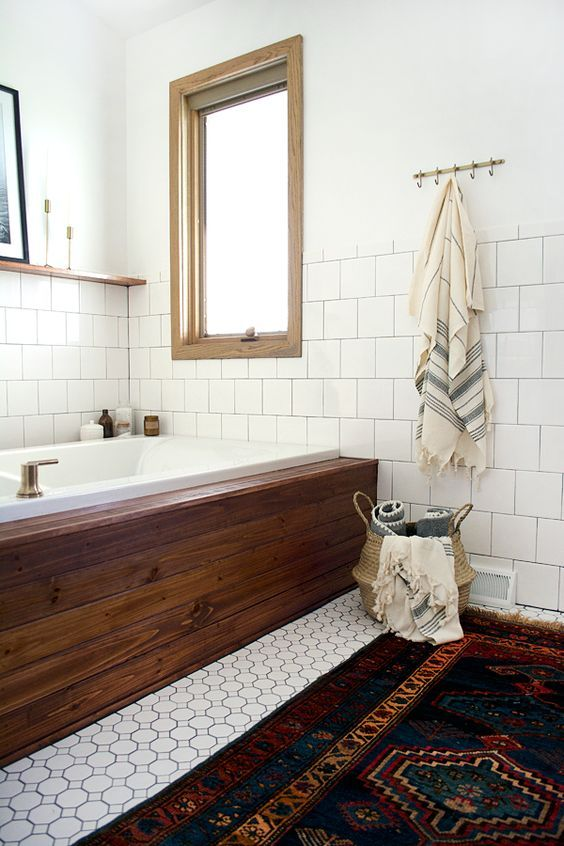 a rich-colored wood clad tub stands out in a neutral bathroom, and a colorful rug matches