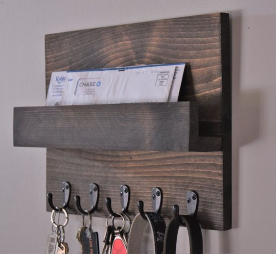 a dark wooden rack with a mail compartment and some hooks to hang keys and bags