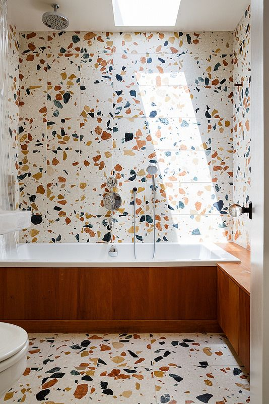 a terrazzo bathroom with a bathtub clad with rich-colored wood and a matching bench