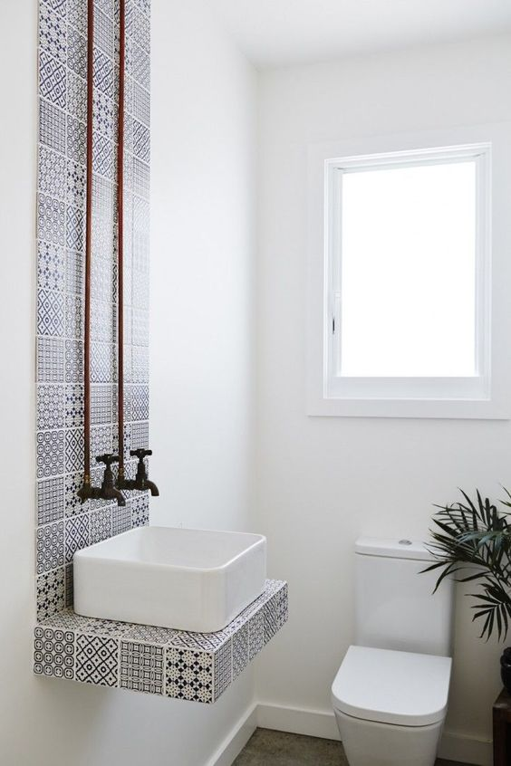 a tiny powder room with a creative black and white mosaic tile backsplash and floating ink stand