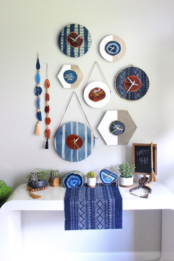 an arrangement of agate clocks and agate slice hangings over the console table