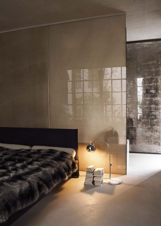 a dark glass space divider separates the bedroom and the closet and keeps the space masculine
