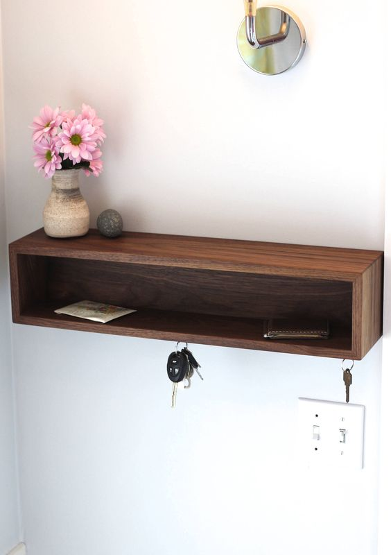a modern wooden box shelf provides storage for various small stuff and some hooks for keys