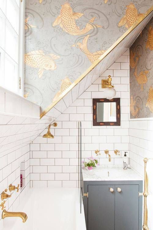 a grey and white bathroom with gold detailing and grey and gold fish print wallpaper