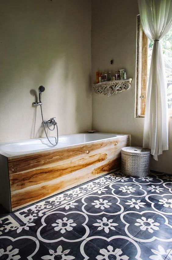 light-colored wood adds a cozy touch to the bathroom and contrasts the mosaic floor