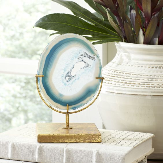 a gorgeous slice of blue agate is mounted on an aged, golden stand to offer natural beauty