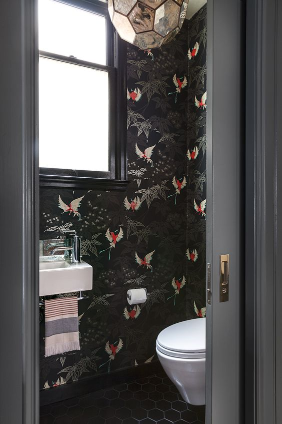 black wallpaper with bold red bird prints to make the powder room wow