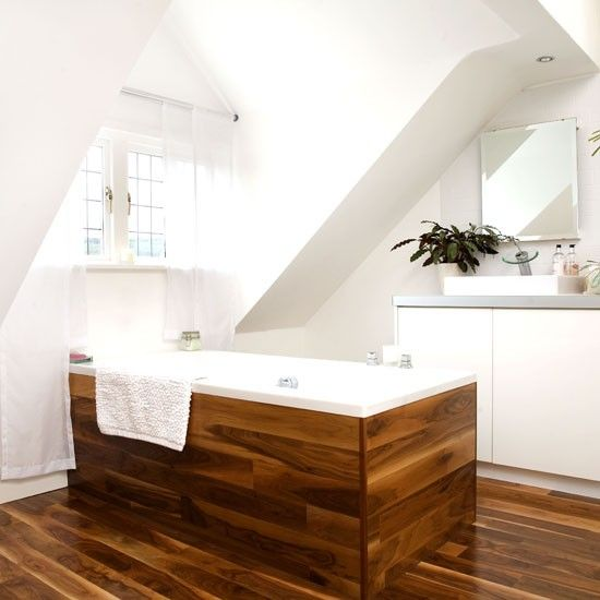 rich-colored wood to clad the floor and the tub stand out in a neutral bathroom