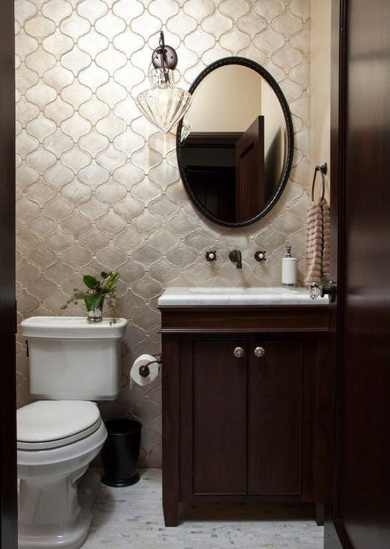 Moroccan tiles of a tender pearly shade accentuate this small powder room