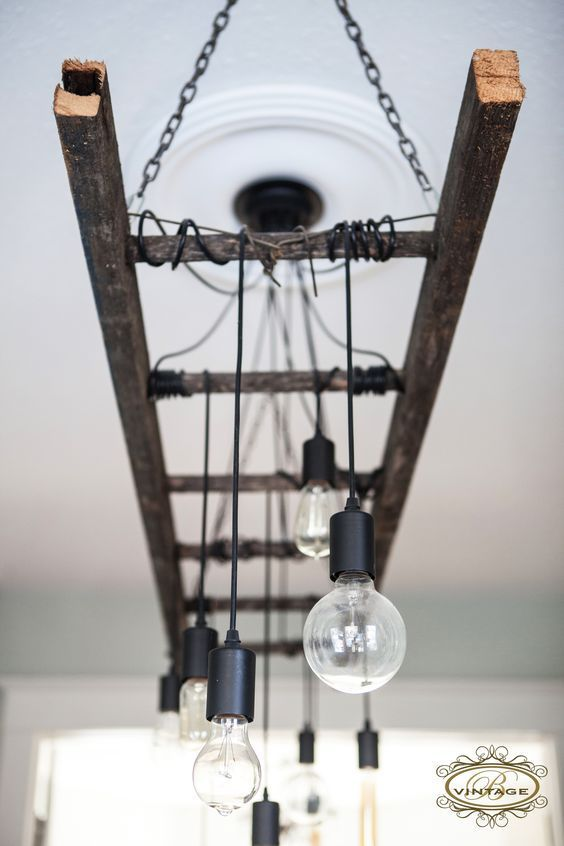 a hanging rustic ladder on chains with bulbs hanging from it as a unique chandelier