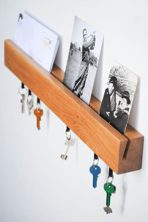 a wooden shelf with a slit for holding mail and photos and some hooks for hanging keys