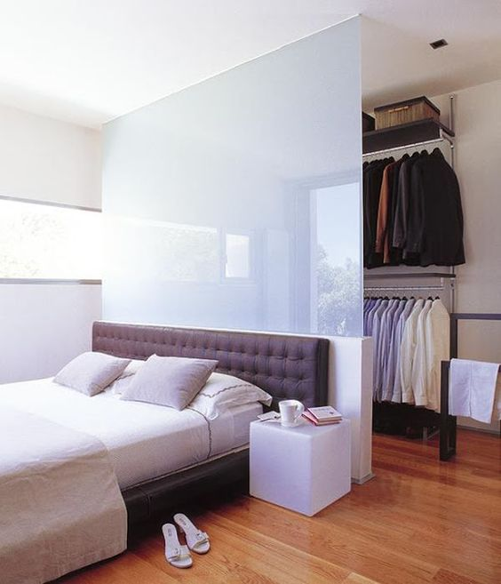 an opaque glass space divider separates the bedroom space from the walk-in closet