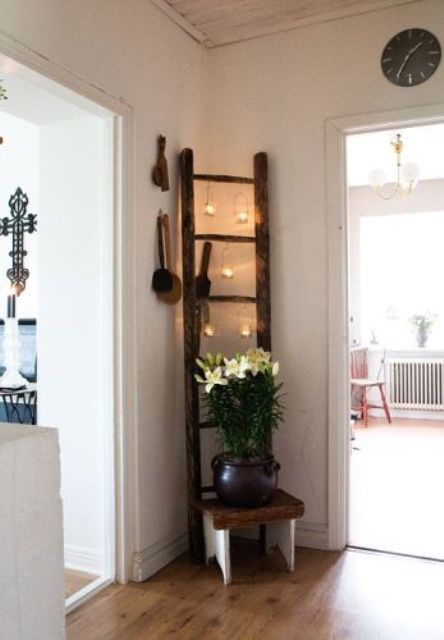 a ladder with hanging candle holders in the corner is a great idea to decorate an awkward space