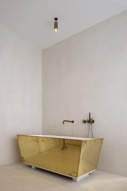 a modern free-standing bathtub covered with a gold sheet for a bolder look