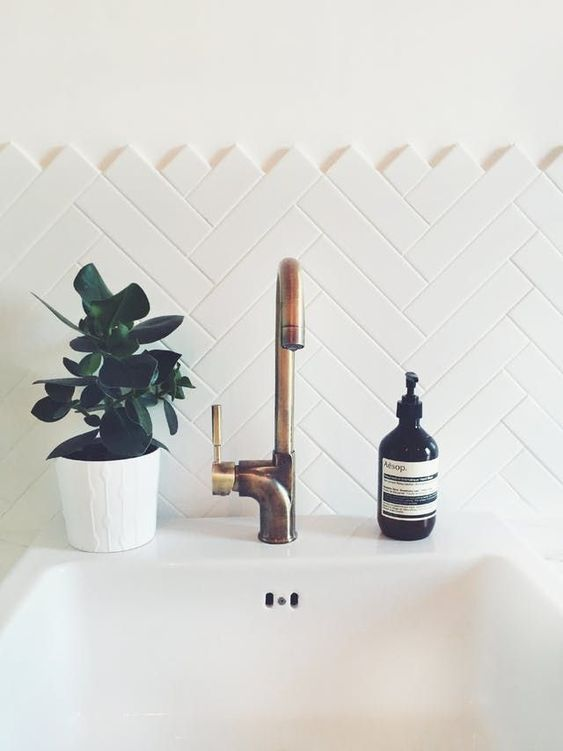 a white tile backsplash done in the chevron pattern adds a texture to the look