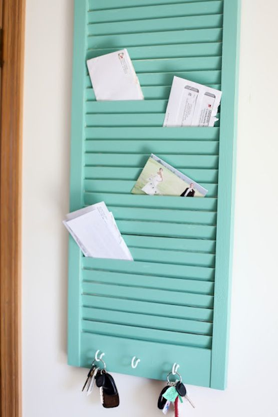 an old shutter painted and transformed into a key rack with enough mail storage