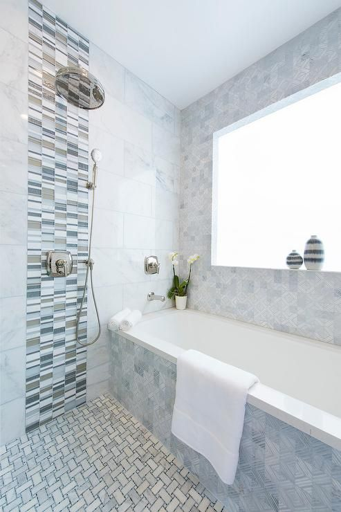 the wall and the bathtub covered with the same grey and blue tiles