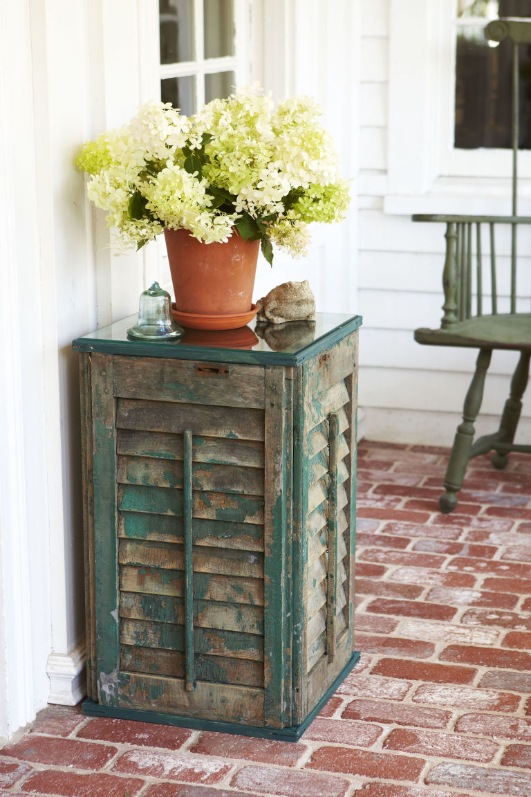 DIY vintage shutter side table with a glass top (via www.goodhousekeeping.com)