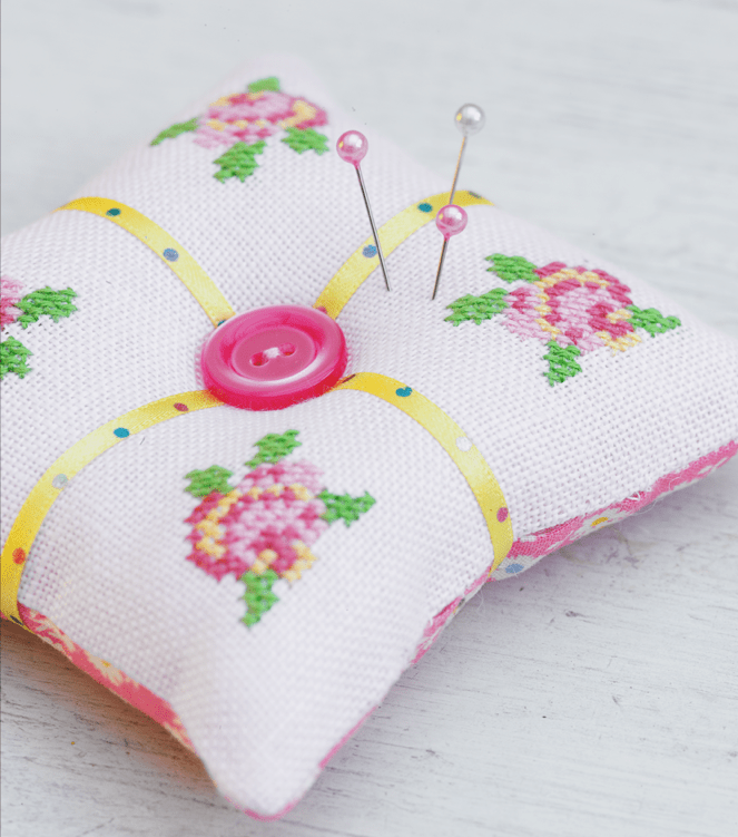 DIY cross stitched roses pincushion with a large button (via ideas.sewandso.co.uk)