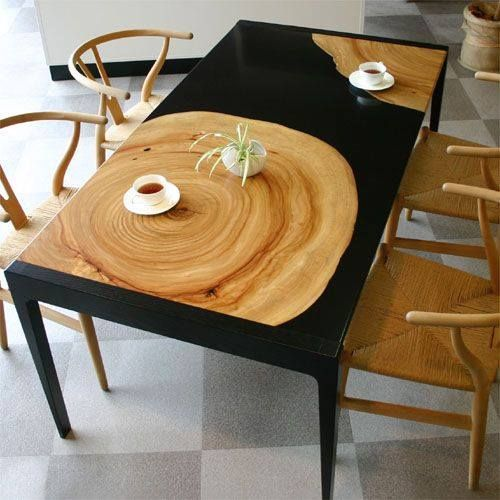 a beautiful black resin and teak pieces dining table and matchign wooden chairs for a bold look