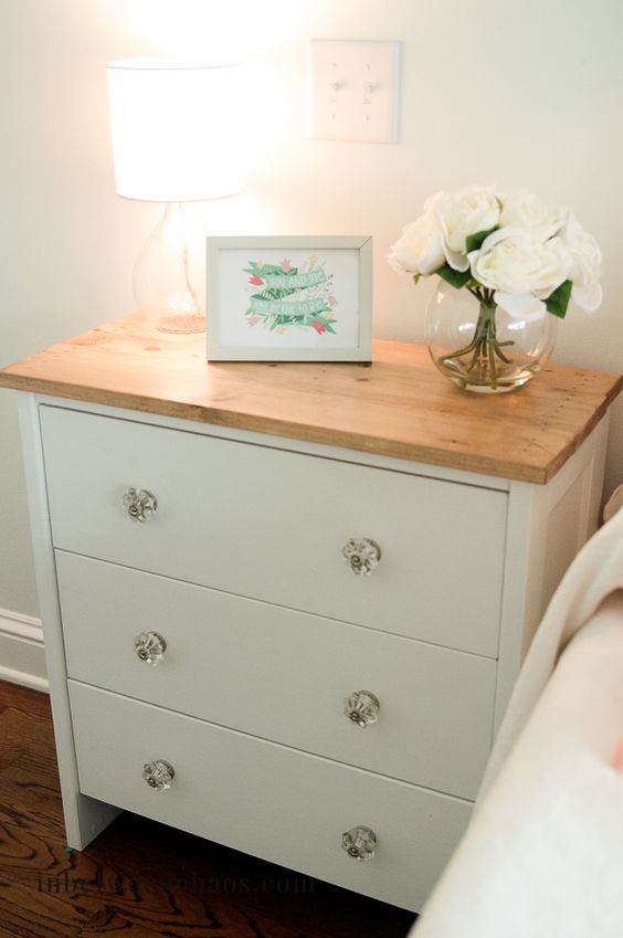a charming nightstand in white, with glass knobs and a wooden countertop of IKEA Rast
