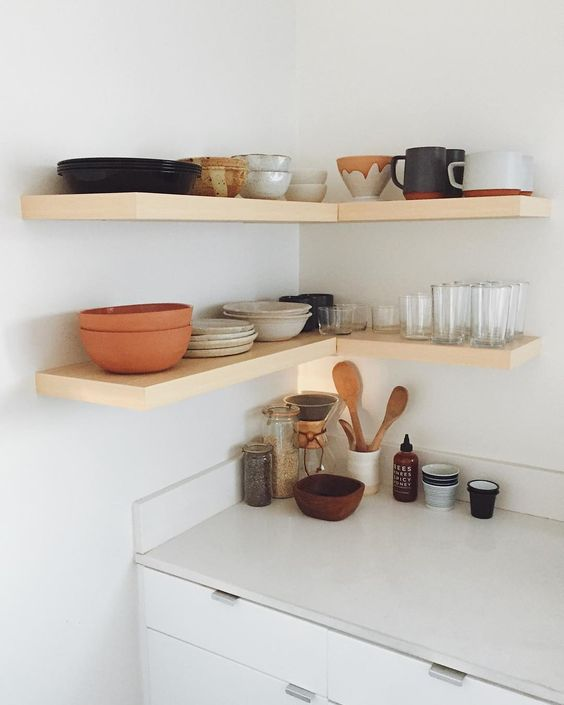 simple wooden floating shelves in the corner create a comfy cooking nook