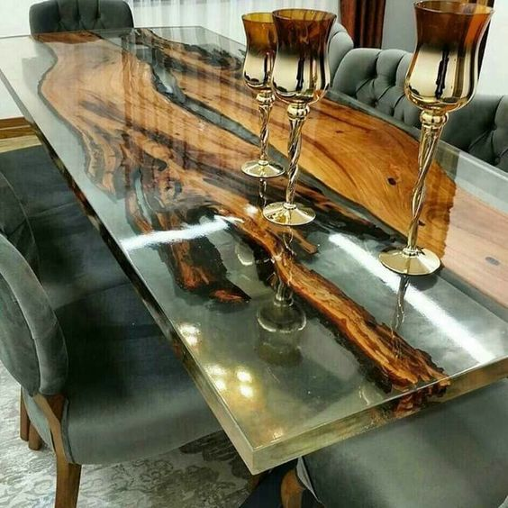 a resin dining table with live edge pieces inside and matching grey upholstery chairs