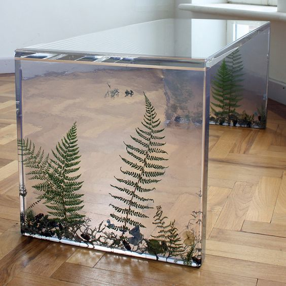 a resin desk with ferns and herbs inside the legs looks very catchy