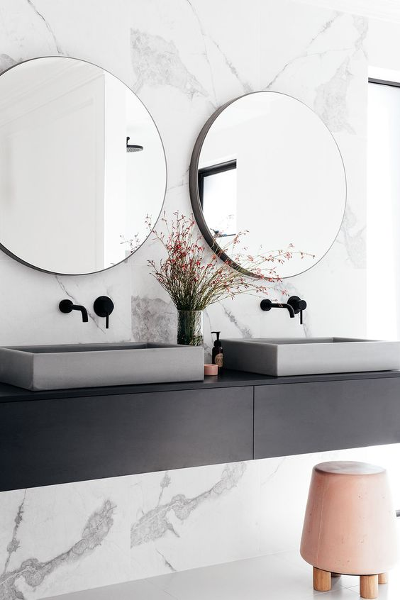 concrete sinks and a pink leather upholstered stool add style to the bathroom