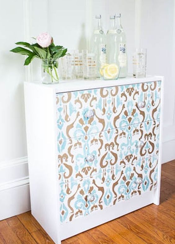 Rast painted white with drawers decorated with printed wallpaper to use as a drink station
