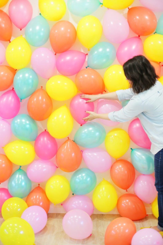 DIY colorful balloon backdrop (via lovelyindeed.com)