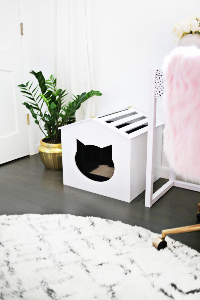 DIY white plywood cat litter box cover with a cat head entry and a striped roof (via abeautifulmess.com)