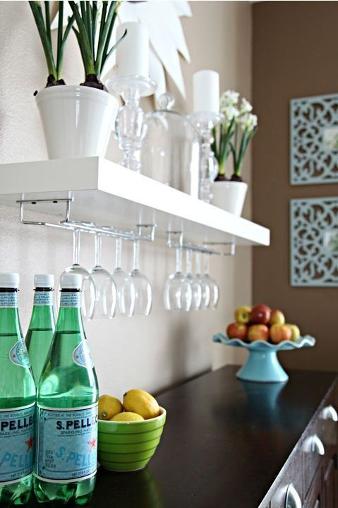 an IKEA Lack shelf with comfy glass holders is an ideal option for a home bar