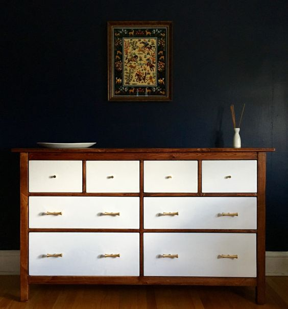a dark stained IKEA Hemnes dresser with white drawers and brass handles for a contrasting look